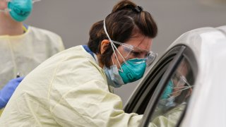 Certified Registered Nurse Kimberly Scheider does a nasal swab on a patient in their car at Penn State Health St. Joseph in Bern Township, Pennsylvania, March 27, 2020.