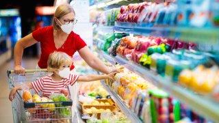 Foto de banco de imágenes que muestra a mujer y su hijo con cubrebocas en un supermercado.