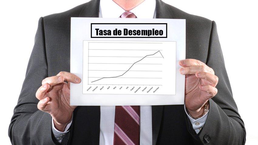 Hombre sostiene hoja con gráfico que muestra tendencia de la tasa de desempleo.