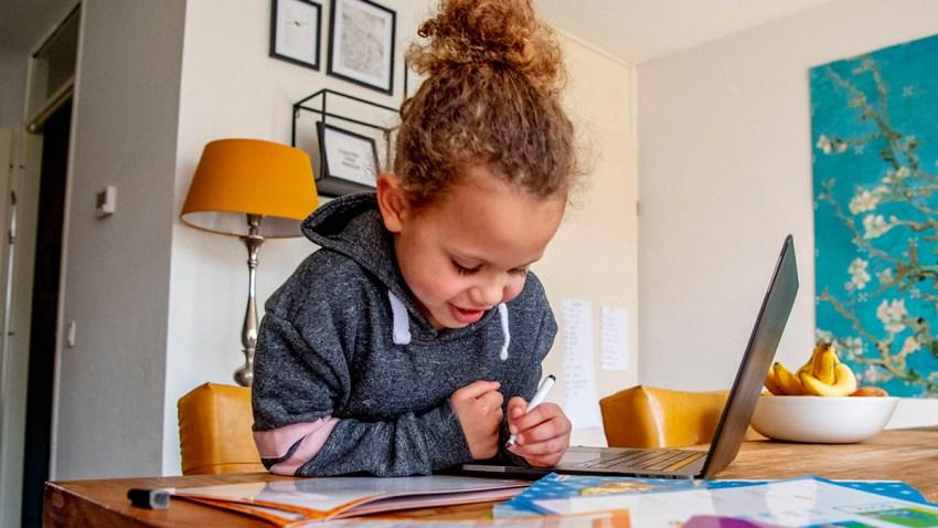 child studies with laptop