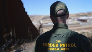 In this Feb. 26, 2013, file photo, a U.S. Border Patrol agent looks along a section of the recently-constructed fence at the U.S.-Mexico border in Nogales, Arizona.