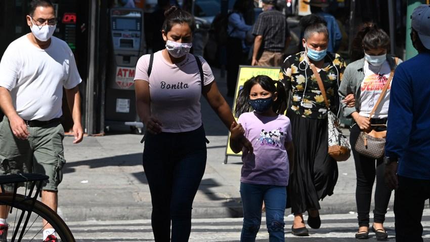 People wearing masks walk on a street in downtown Los Angeles.