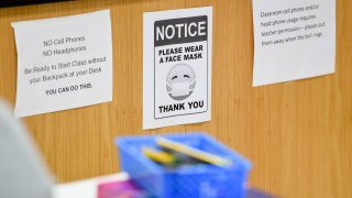 "West Lawn, PA - October 22: A sign in a classroom that reads ""Notice, please wear a face mask. Thank you"" next to signs about rules of cell phone usage in class. At Wilson High School in West Lawn, PA Thursday afternoon October 22, 2020 where the school has been taking precautions for students doing in person school to prevent the spread of Coronavirus / COVID-19."