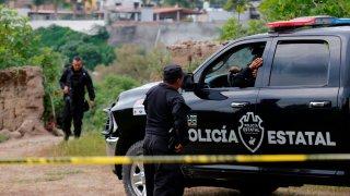 Un par de policías vigilan un paraje en el que hallaron muertos a tres hermanos
