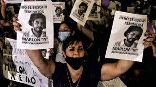 Una mujer, rodeada de más mujeres, alza sus brazos para mostrar dos carteles de un presunto femenicida